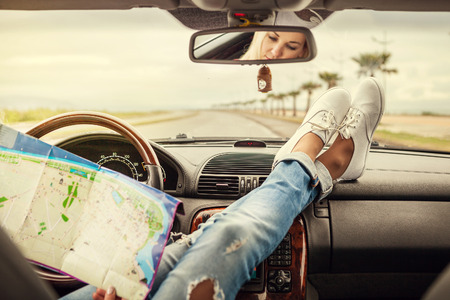 car navigation: Young woman alone car traveler with map