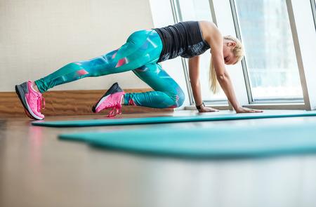 Schöne blonde Frau macht Fitness-Übungen in modernen Fitnessraum Standard-Bild - 38957713