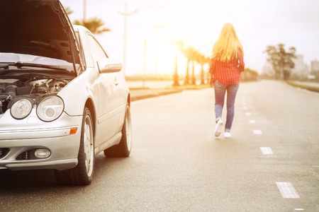 Upset blonde woman leaving her broken roadster Banque d'images