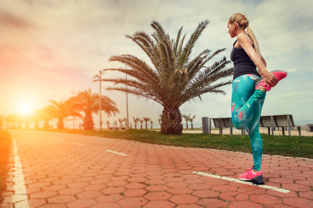 warm up: Young woman warm up legs before start jogging Stock Photo