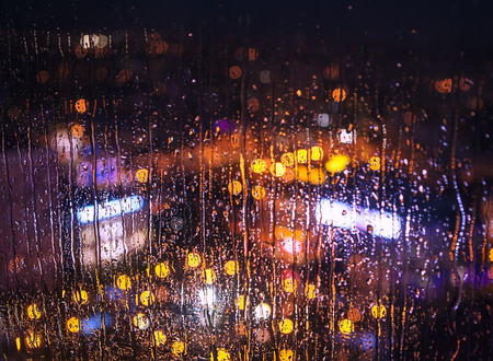 colorful lights: Night city lights behind rainy window Stock Photo