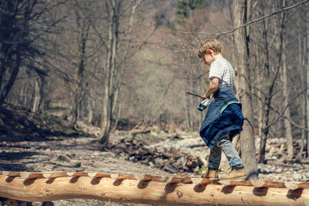 bridge over water: Boy goes on the mountain river bridge in spring forest Stock Photo