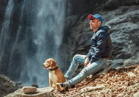 Muž se psem sedí poblíž vodopádu Reklamní fotografie