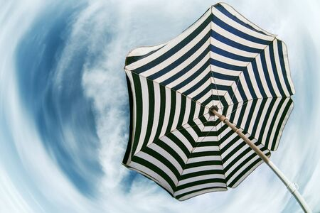 fish eye: Striped  beach umbrella over blue sky fish eye view
