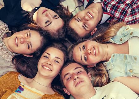 Teenage friends lying together in circle Standard-Bild
