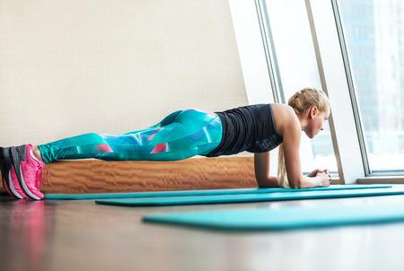 ジムで板の静的運動をしている金髪の女性 写真素材
