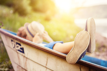kayak: Boy lying in old boat in the lake coast close up image Stock Photo