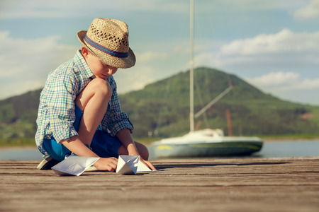 Little boy make paper boats sitting on the wooden pier