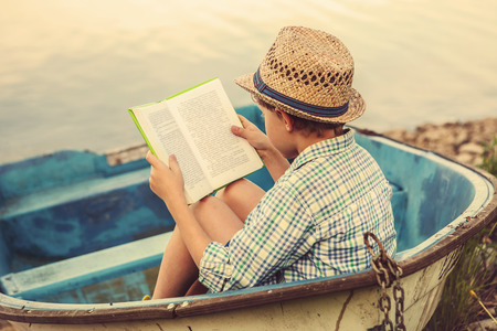 kids reading book: Reading boy in old boat