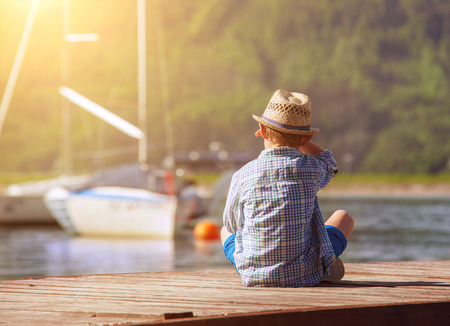 wooden dock: Boy on wooden pier looking for a yahts