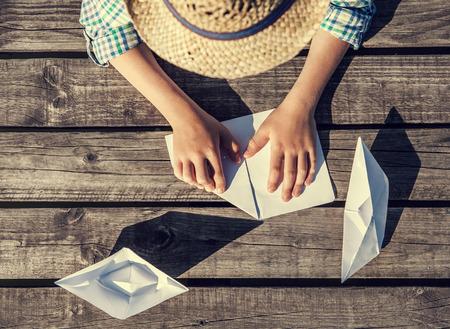 craft paper: Cierre de la imagen del muchacho manos haciendo un barcos de papel Foto de archivo