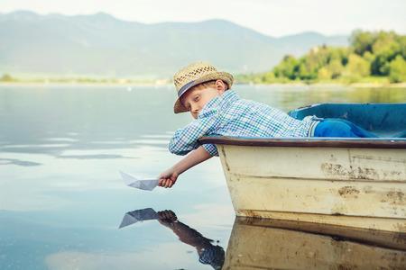 Jongetje lancering papier schip liggen in oude boot Stockfoto