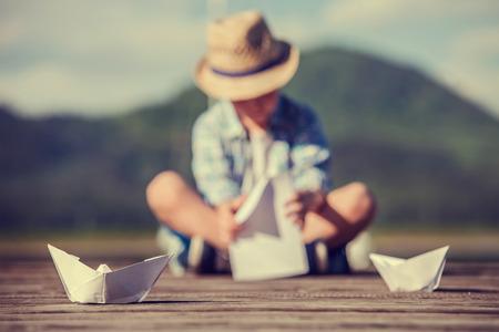 bateau: Boy faire un bateau de papier assis sur la jetée en bois Banque d'images
