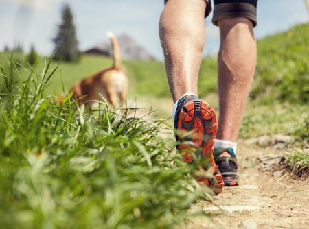 hacer footing: Las piernas del hombre en el sendero de montaña cerca la imagen Foto de archivo