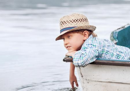 straw hat: Boy in straw hat lying in old boat