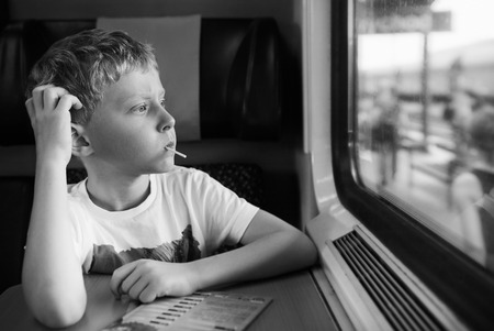 Bored boy with candy look in train window photo
