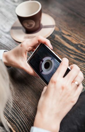screen shot: Woman taking a picture her coffe cup with modern phone