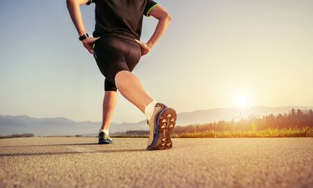 close up image: Warming up runner on the road close up image
