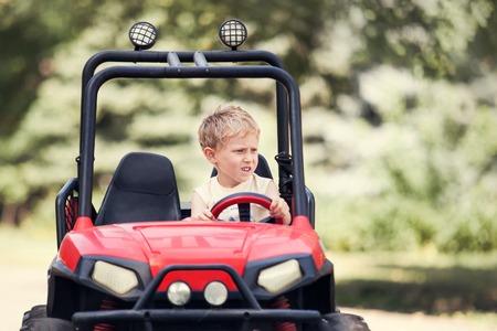 drive car: Little boy drive a mini electric car in park