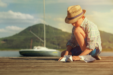 free time: Little boy make paper boats sitting on the wooden pier