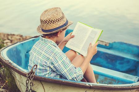 chaloupe: Gar�on lisant dans le vieux bateau