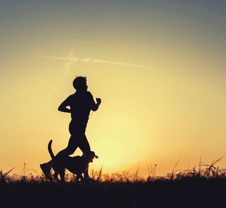 perro corriendo: Corredor de la noche con el perro Foto de archivo