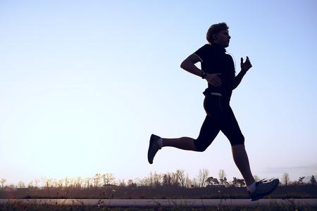 Het silhouet van runner in zonsondergang opkomst Stockfoto