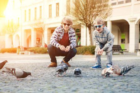 paloma: Dos hermanos alimentan a las palomas en la plaza de la ciudad vieja