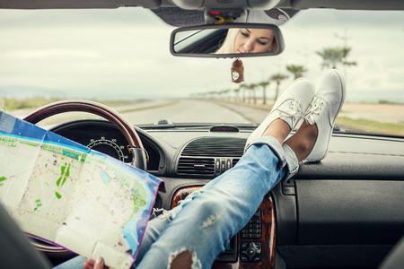 trips: Young woman alone car traveler with map