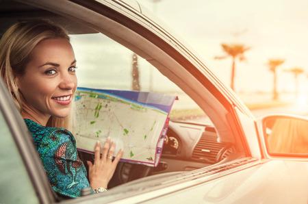 Mooie jonge vrouw die in de auto zit met een wegenkaart Stockfoto