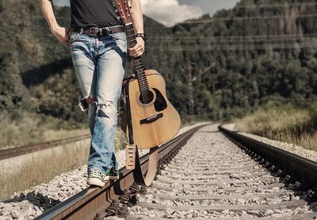 mezclilla: Cierre de la imagen piernas del hombre en pie de mezclilla rippad en el ferrocarril