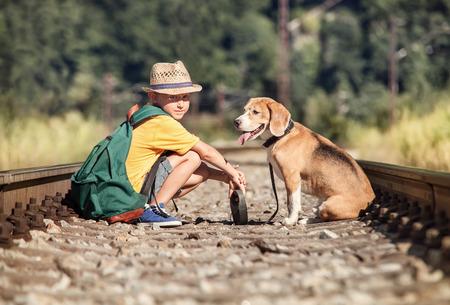 dog days: Muchacho con su perro sentado juntos en el ferrocarril