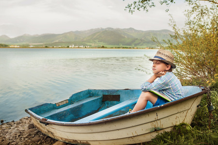 Dreaming boy in old boat at the lake coast