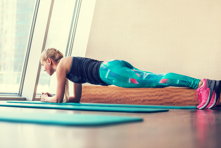 attractive female: Blonde female doing plank static exercise in gym