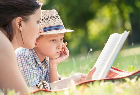 Mother read a tales for her son in summer garden