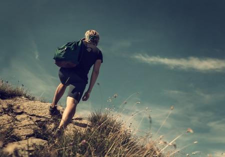 男は山の丘の上に登る 写真素材