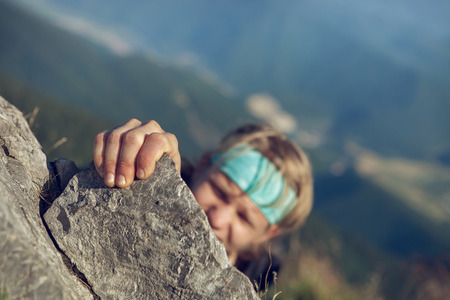 hand free: Young man finishing his extreme mountain climb Stock Photo