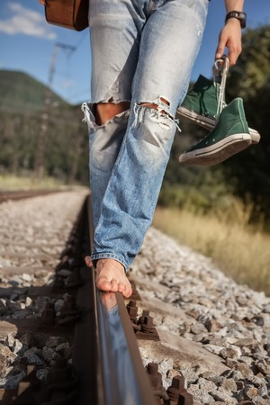 ripped jeans: Young man barefoot  legs in ripped jeans close up image