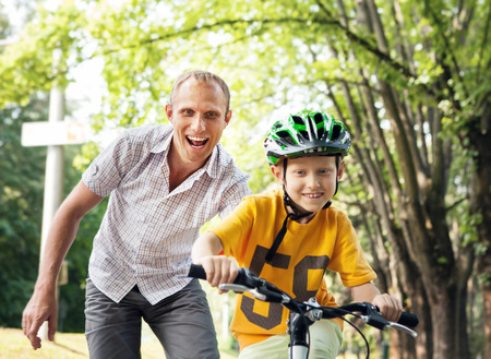 father and child: Father learn his son to ride bicycle