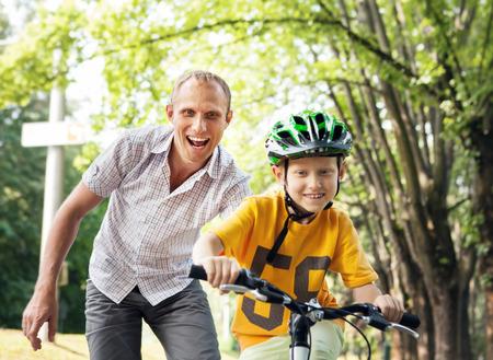 Vader leert zijn zoon te fietsen Stockfoto