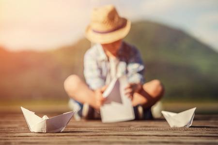 少年は、木製の桟橋の上に座って紙船を作る 写真素材