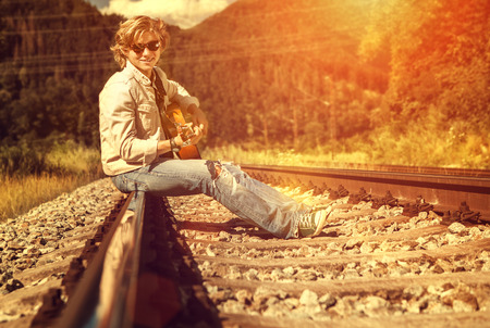 rips: Happy smiling young man with guitar sitting on railway