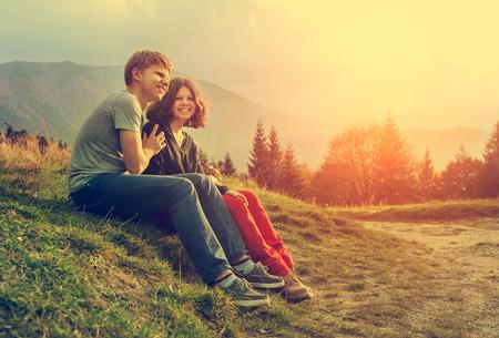 sol radiante: Pareja de jóvenes sentados juntos en la puesta de sol
