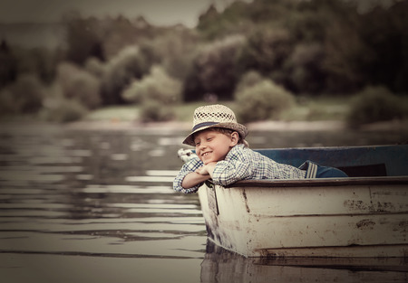 dream lake: Little boy in old boat on the calm lake surface