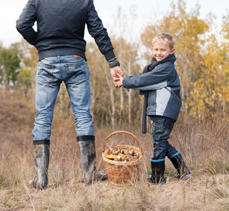 Smiling little boy with a his father on the mushroom picking Stock Photo