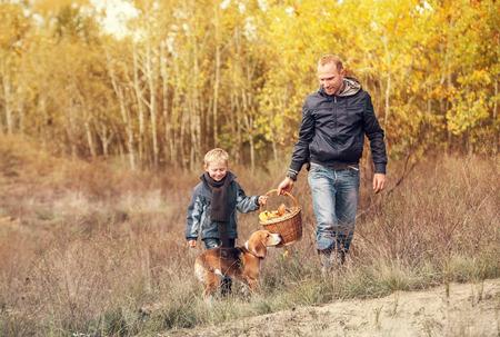 hongo: Hijo con el padre lleve completa cesta de setas en el bosque de otoño