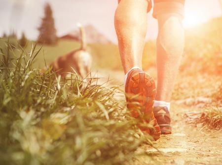 dog running: Las piernas del hombre en el sendero de montaña cerca la imagen Foto de archivo