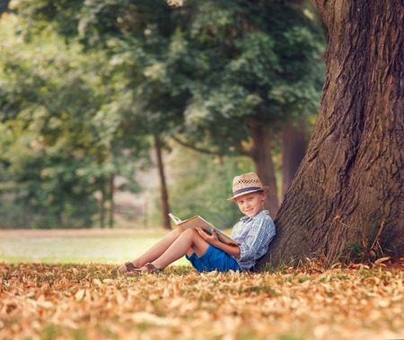 Boy with book sitting under tree in park