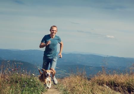 자신의 강아지와 함께 산악 지대에 달리는 남자 스톡 콘텐츠