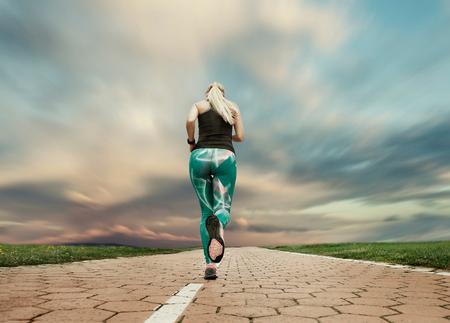 mujer deportista: Joven rubia chica correr de noche con gran celaje Foto de archivo